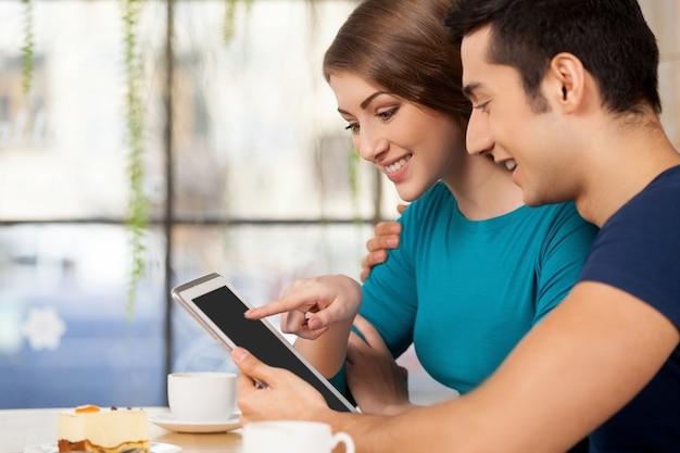 디지털 태블릿과 커플. 레스토랑에 앉아서 디지털 태블릿을 사용하는 쾌활한 젊은 부부의 측면 보기