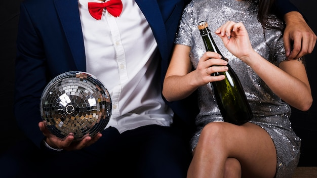 Couple with disco ball and bottle of champagne