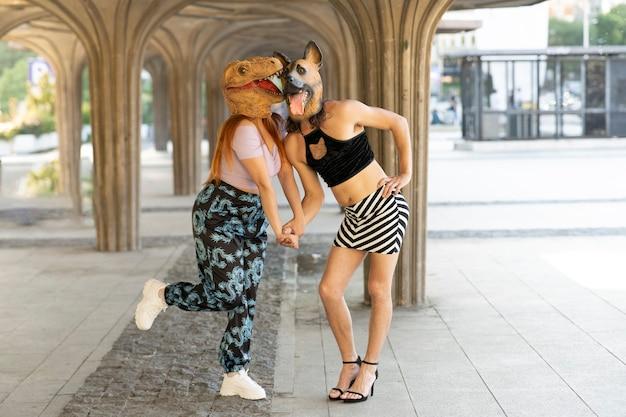 Пара с собаками и масками динозавров, абсурдная и забавная концепция тренда