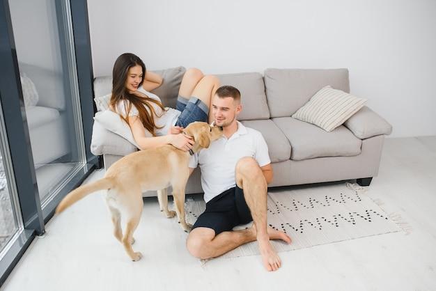 Пара с собакой, сидя дома