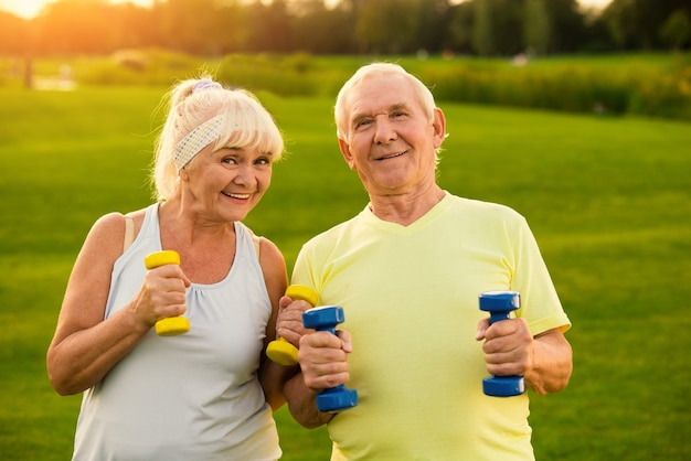 Couple with dumbbells is smiling