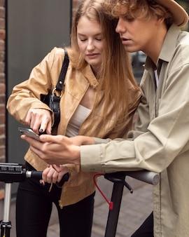 Пара с электросамокатами и смартфоном на открытом воздухе