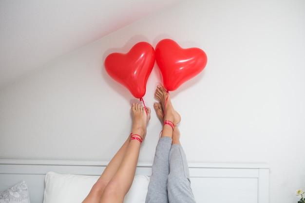 벽에 발을 가진 커플과 그의 발로 풍선을 들고