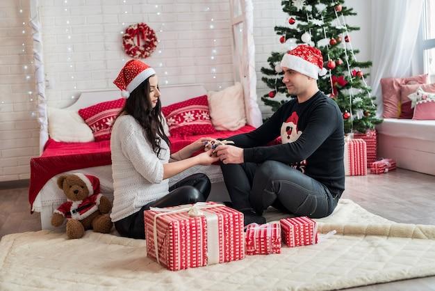 Couple with fir tree at christmas studio