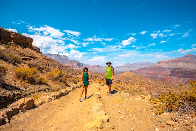 A couple with green shirt resting on the south kaibab trailhead trekking. grand canyon