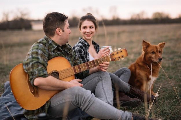 カップルはギターとかわいい犬