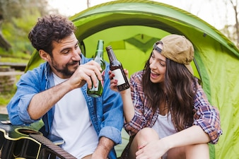Couple with guitar clinking bottles