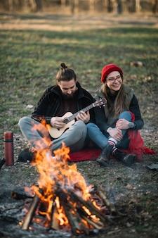 キャンプファイヤーの近くのギターとカップルします。
