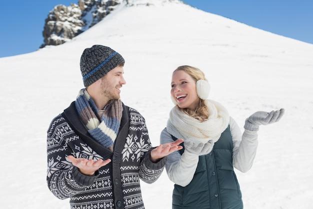 Пара с открытыми руками, глядя друг на друга перед заснеженным холмом