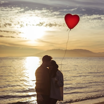 Couple with heart balloon hugging on sea shore in evening