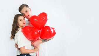 Couple with heart balloons hugging