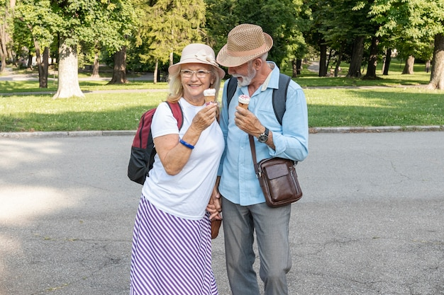 Couple with ice cream in hand walking through park