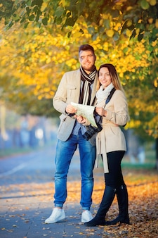 Couple with map and camera in city autumn alley.