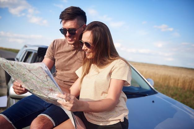 도로 여행에 가장 적합한 도로를 선택하는 지도를 가진 커플
