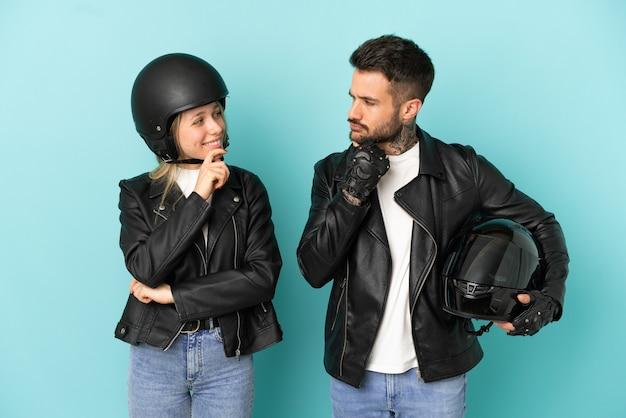 お互いを見ている孤立した青い背景の上のオートバイのヘルメットとカップル