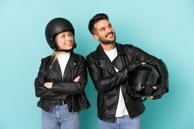 笑顔で見上げる孤立した青い背景の上のオートバイのヘルメットとカップル