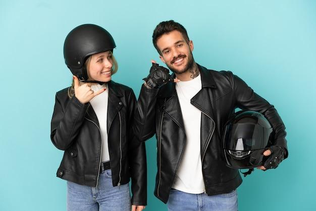 電話のジェスチャーを作る孤立した青い背景の上のオートバイのヘルメットとカップルします。コールバックサイン