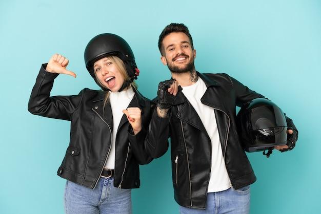 孤立した青い背景の上のオートバイのヘルメットとカップルを誇りに思って、自分自身の概念を愛して自己満足