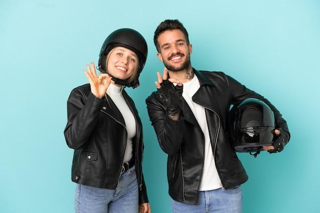 Пара с мотоциклетным шлемом на изолированном синем фоне, показывая пальцами знак ок