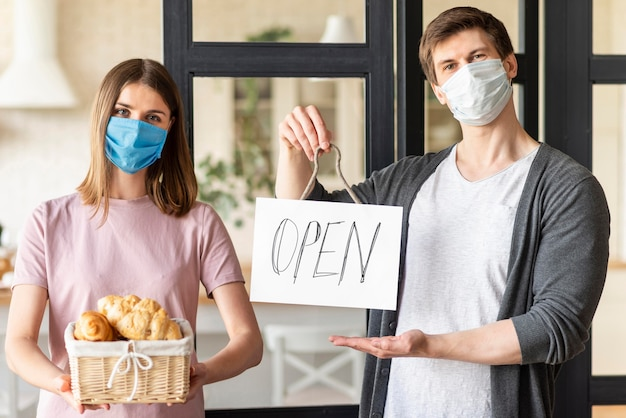 Couple with open sign and medical mask
