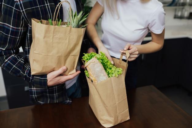 キッチンで食料品でいっぱいのパッケージとカップル