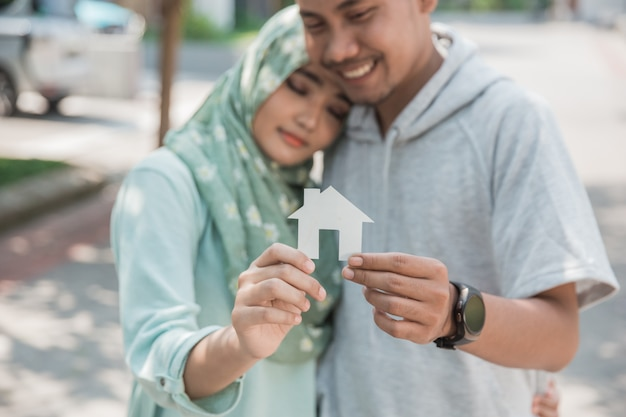 Couple with paper of house