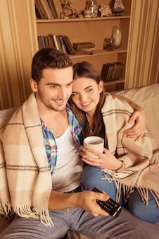 Пара с пледом и чашками, расслабляясь на диване