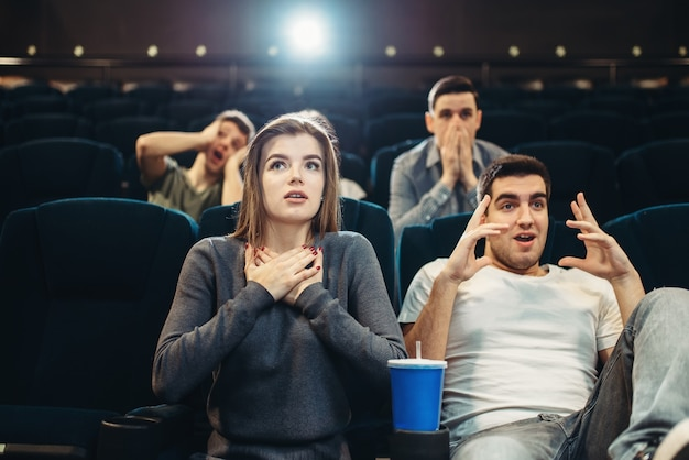 Couple with popcorn fascinated watching the film in cinema. showtime, entertainment industry