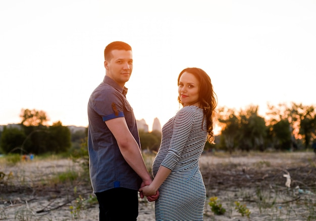 Couple with pregnant woman holding hands on sunset
