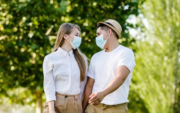 Пара с защитной маской гуляет в парке