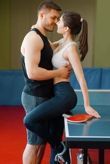 卓球台で抱き締めるラケットとカップルします。