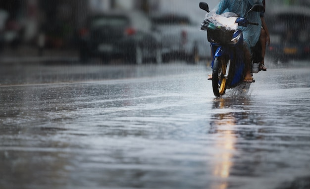 A couple with raincoat on a motorbike during hard rainfall. selective focus and very shallow depth of field composition.