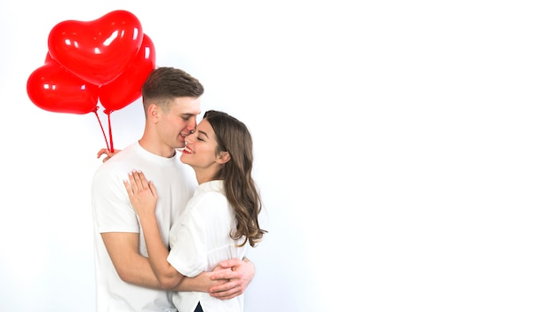 Couple with red heart balloons hugging