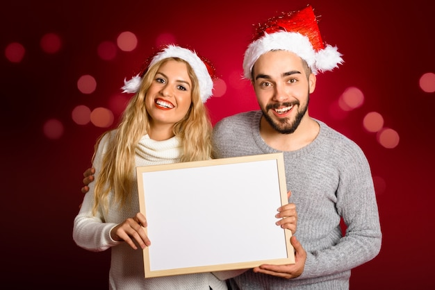 Couple with a santa's hat holding a blank board on red background