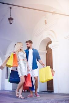 街の通りで買い物袋とカップル