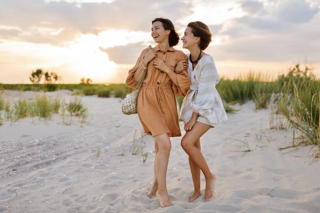 해변에서 포즈를 취하는 린넨 여름 옷에 짧은 헤어 스타일을 가진 커플