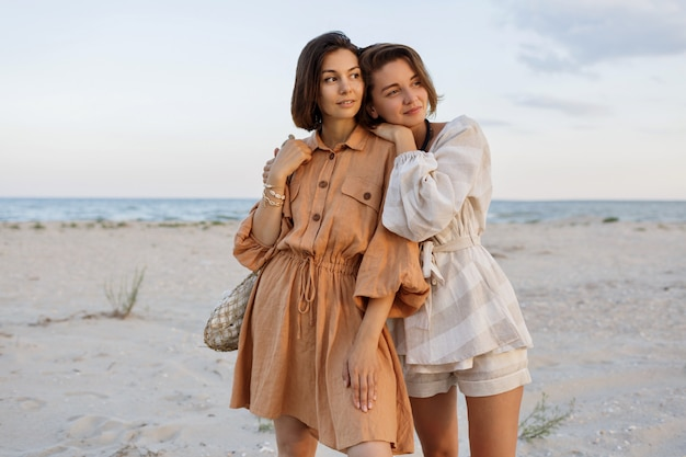 Couple with short hairstyle in linen summer clothes posing on the beach
