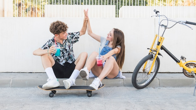 Couple with skateboard holding juice and giving high five
