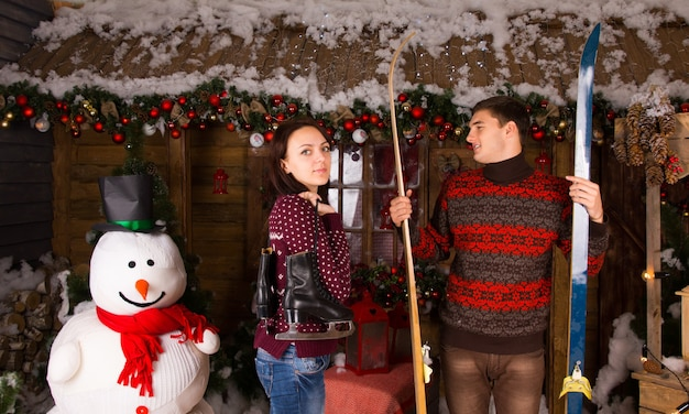 Couple with skates and skis standing next to snowman in front of log cabin