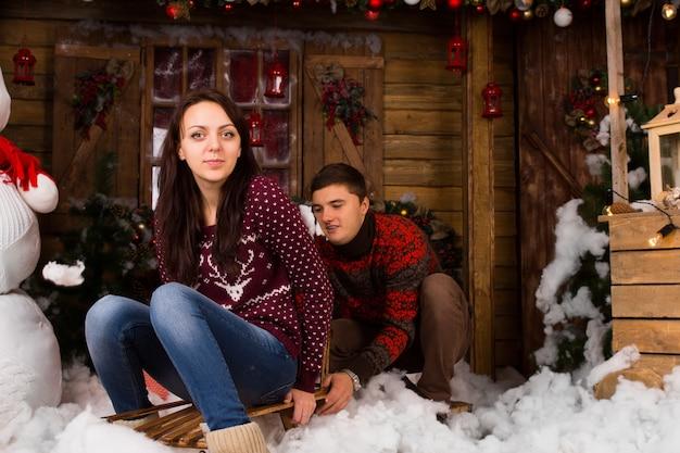 통나무 집 앞 겨울에 야외 썰매와 커플