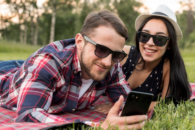 Couple with a smartphone on a picnic blanket
