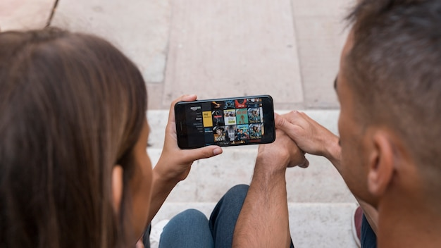 Couple with smartphone showing amazon prime video app