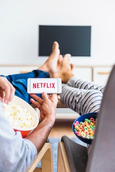 Couple with snacks watching netflix series in living room