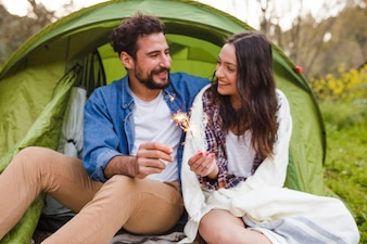 Couple with sparklers relaxing in nature