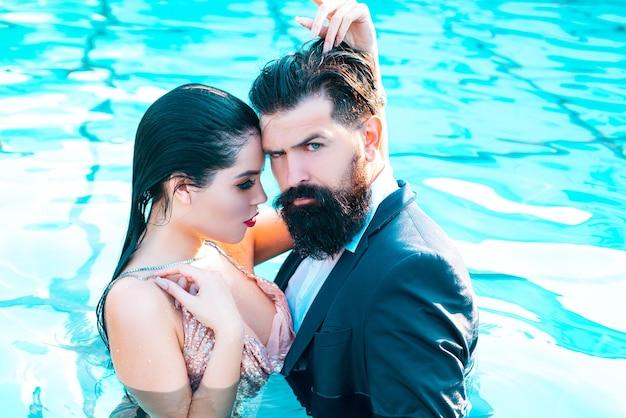 スイミングプールでスーツとカップル最高のセックスを抱きしめる美しい官能的な若いカップル...
