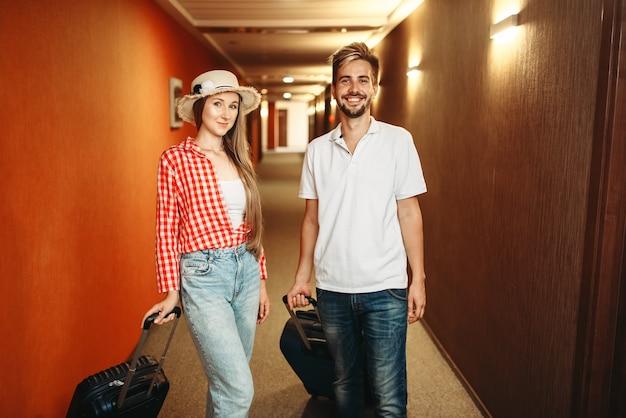 ホテルにチェックインするスーツケースとカップル