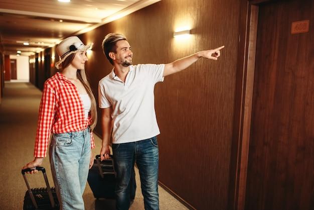 Пара с чемоданами ищет свой номер в отеле