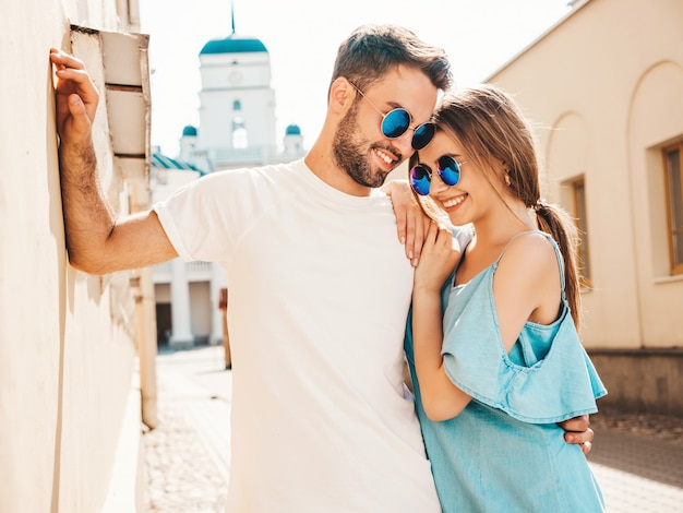 Couple with sunglasses posing in the street