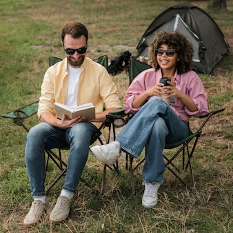 Couple with sunglasses reading and drinking while camping outdoors