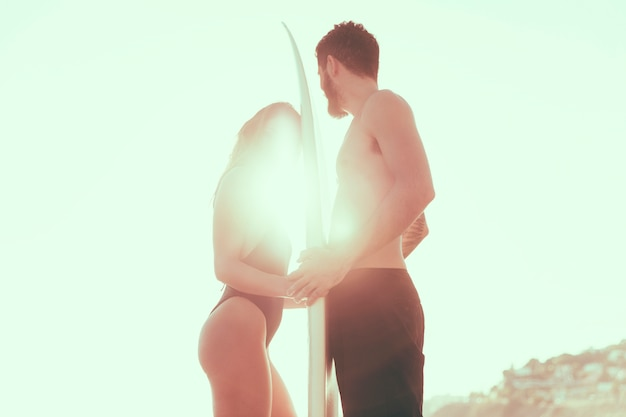 Couple with surfboard against bright sun